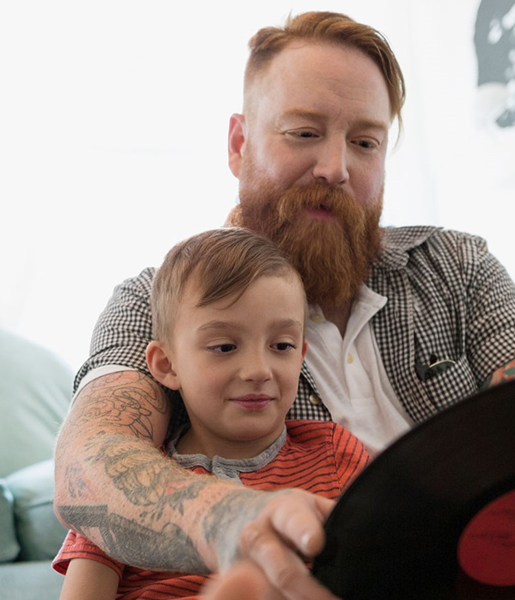 Father And Son Looking At Records On Living Room Floor