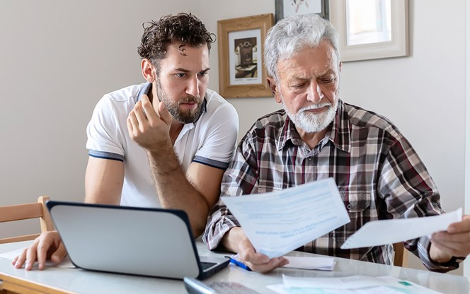 Adult Son With His Troubled Father Discussing Finance Budget Paperwork