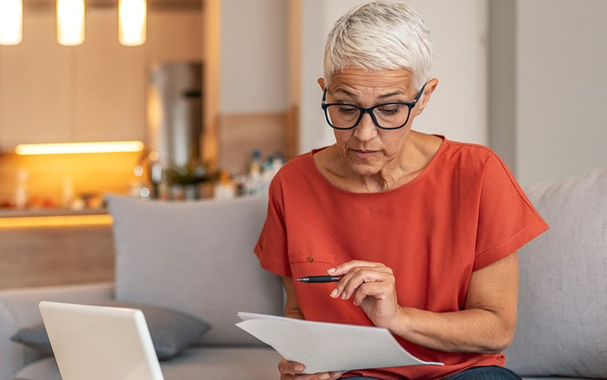 Woman Using A Laptop And Checking Finances At Home
