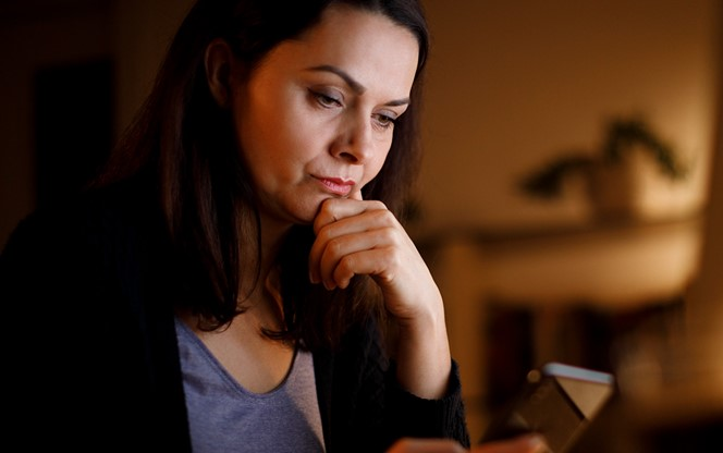 Worried Mature Woman Working Late At Home Looking At Her Phone